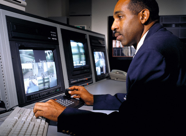 Security Guard Watching Security Videos --- Image by © Brian Donnelly/Corbis